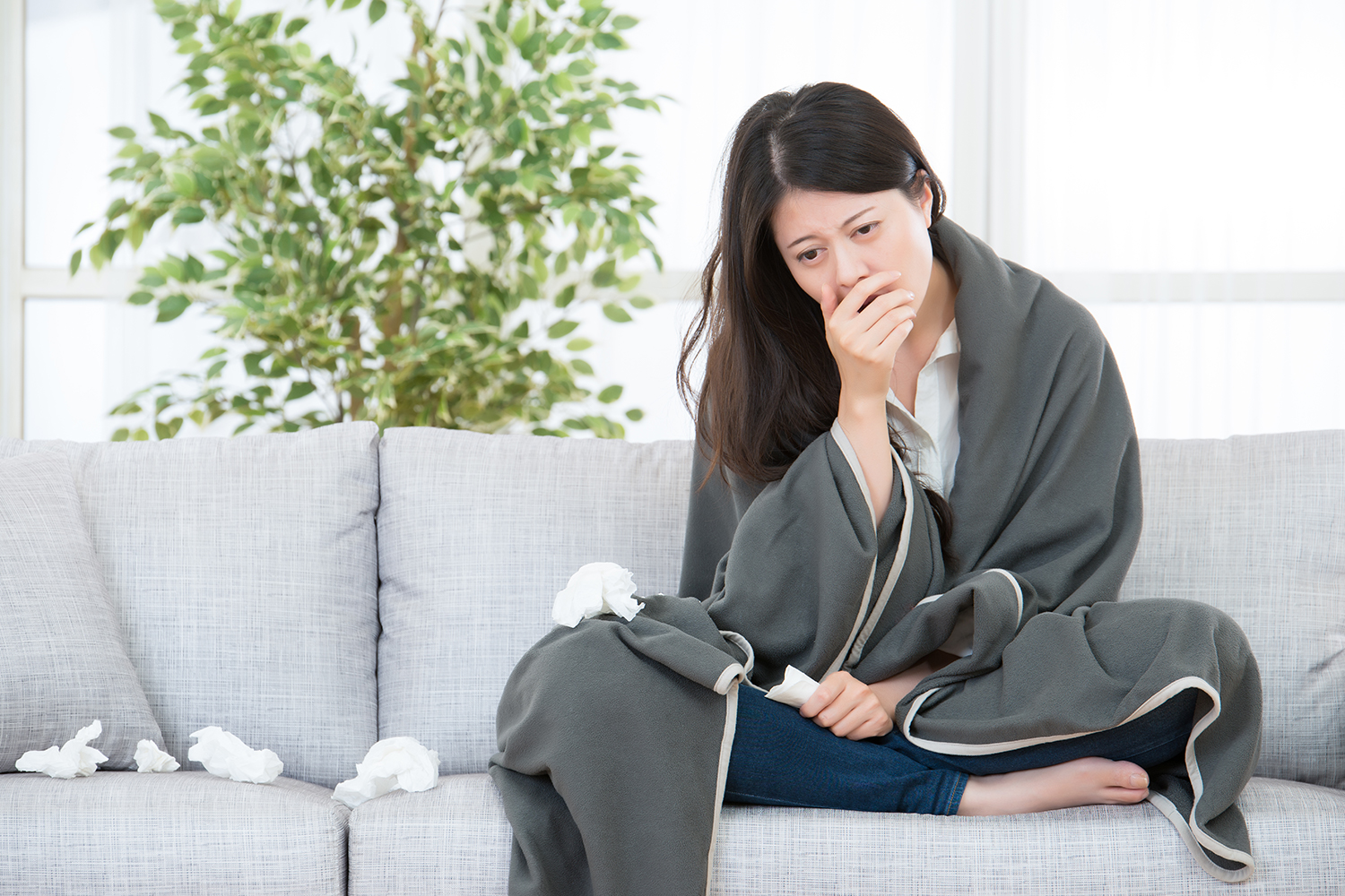 A woman on the couch with a blanket and a pile of tissues
