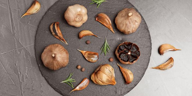 Slate plate with aged black garlic and rosemary on gray background, top view.